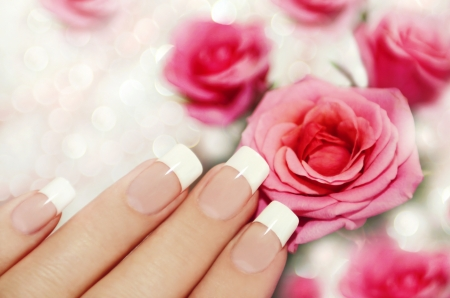 red nail: French manicure on a woman s hand with pink roses on a brilliant