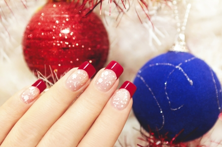 Beautiful winter manicure with snow and red lacquer on new year balls