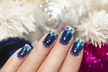 christmas manicure: Winter blue manicure with snowflakes and pink triangular rhinestones near the white tree and colorful shiny balls