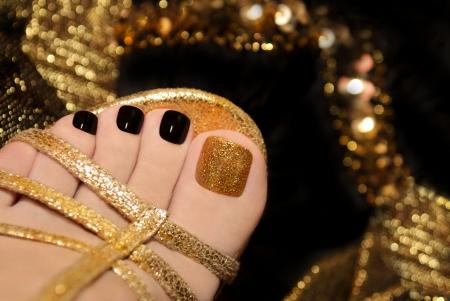 pedicura: Pedicura de lujo con lacado negro y el oro en los dedos del pie de las mujeres s en el fondo negro y brillante