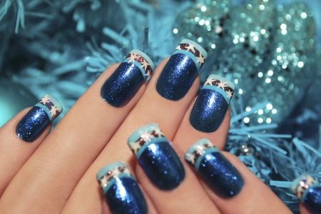 Beautiful winter blue manicure with snowflakes on a brilliant background in the form of snowflakes   Stock Photo