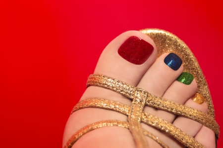 Beautiful multicolored pedicure on female leg on a red background  Stock Photo