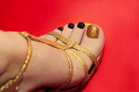 Beautiful luxury pedicure with black and gold brilliant varnish on a red background in gold sandals  Stock Photo