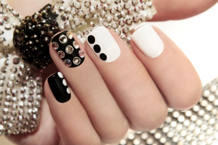 nail art: Manicure on short nails covered with black and white lacquered with rhinestones on a black background
