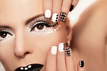 unas largas: Maquillaje con pedrer�a y manicura en colores blanco y negro en la chica Foto de archivo