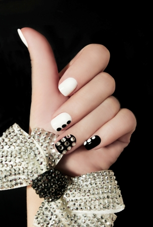Manicure on short nails covered with black and white lacquered with rhinestones on a black background
