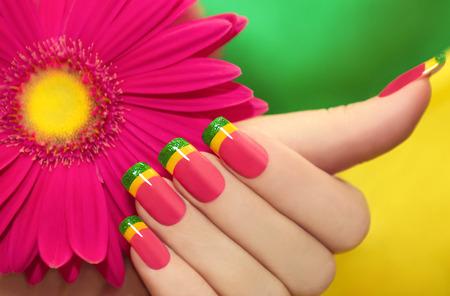 Veelkleurige manicure met roze, gele en groene lak tegen de achtergrond met gerbera's