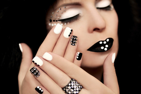 rhinestones: Makeup and manicure with rhinestones on a beautiful young girl on a black  Stock Photo