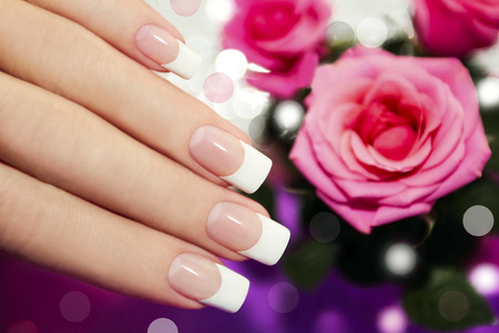 Classic French manicure on a woman s hand with pink roses