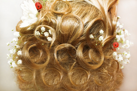 hair part: Beautiful light hairstyle on light hair swirled with the decoration of flowers on a woman s head from behind  Stock Photo