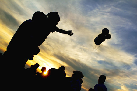 On the feast of the child at the hands of men reaching for balloons evening at sunset  photo