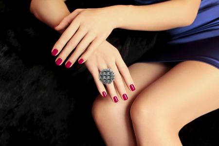 Beautiful Burgundy manicure on female hands with ornament on a black background  photo