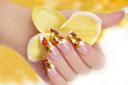 Nail with a pattern of yellow orchids on a long shaped nails  Banque d'images