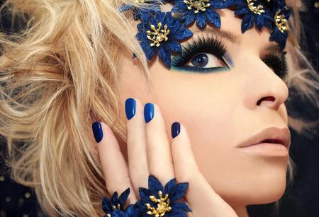 uñas pintadas: Manicura azul de lujo y maquillaje de una niña con el pelo rubio y flores decorativas en un fondo oscuro