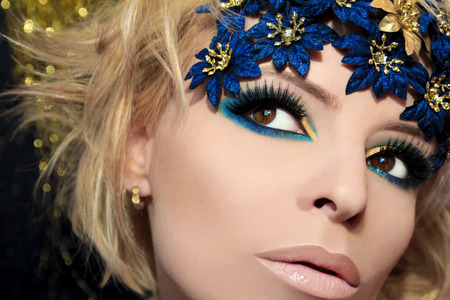 Luxurious blue makeup on a girl with blond hair and decorative flowers on her head  photo