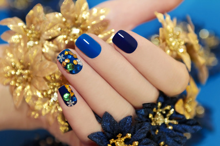 nail art: Nails of women covered in blue lacquer different shades with rhinestones and with flowers in his hand  Stock Photo