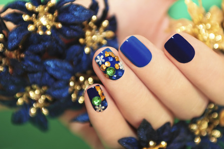 Nails of women covered in blue lacquer different shades with rhinestones and with flowers in his hand  Stock Photo