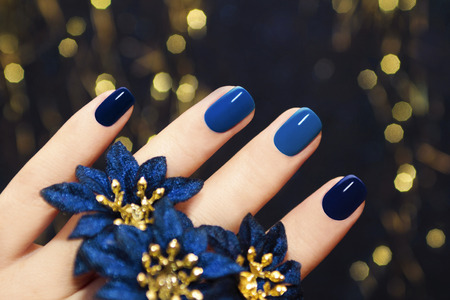 enhancement:    Manicure on women s hands are covered with blue lacquer two tones with flowers
