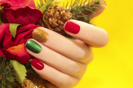 christmas manicure: Multicolor manicure with red,green and yellow brilliant varnish for the nails on a yellow background with rose and Christmas tree