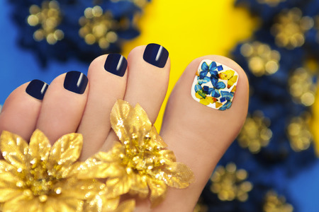 황금 꽃과 흰색 래커 엄지 발가락에 나비와 블루 페디큐어 스톡 콘텐츠