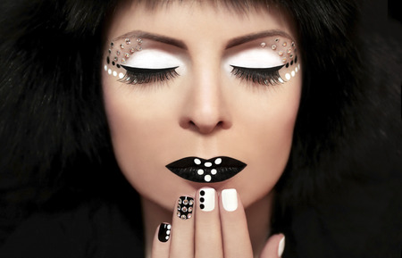 Black and white make-up on the girl with rhinestones on the face and nails  photo