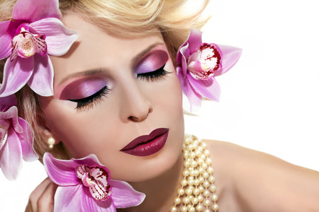 Cherry pink make up the girl with blond hair with flowers and orchids on a white background  photo