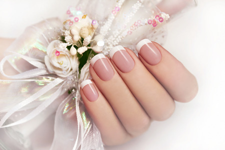nail salon:   Wedding manicure on female hand with festive decoration of white ribbons and flowers