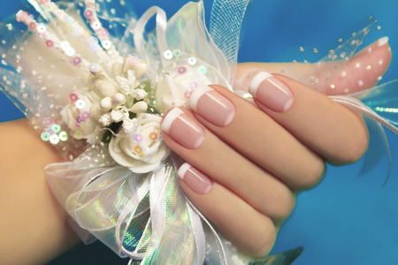 acryl:  Wedding manicure on female hand with festive decoration of white ribbons and flowers