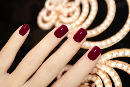 Luxury short manicure Burgundy with jewelry with crystals on a black background  photo