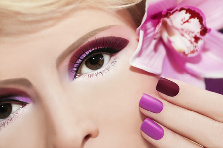 Burgundy and purple makeup and nails on the girl with Orchid  photo