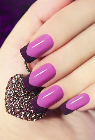 nail salon:     Two-tone French manicure pink and purple with decoration in the form of heart