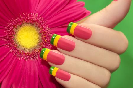 Farbiger Nagellack auf weibliche Hand mit Gerbera in der Hand auf einem grünen