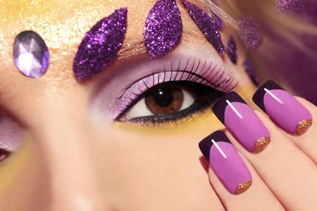 Purple makeup and nails with gold sequins and decoration in the form of leaves