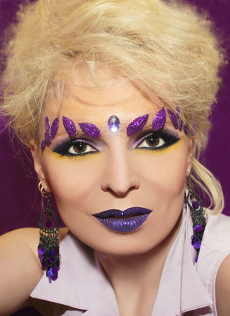 Purple makeup with glistening lips and leaves on the brow of a girl with blond hair  photo