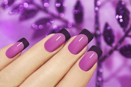 Lilac manicure on female hand with purple sparkles