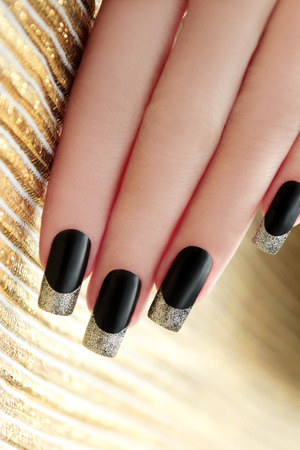 Black French manicure with Golden shining varnish on striped background  Stock Photo