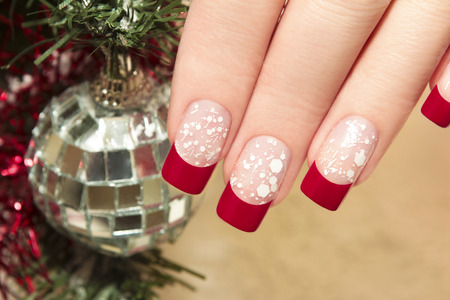 christmas manicure:     Red nail Polish on artificial nails with white crumb and new year s accessories