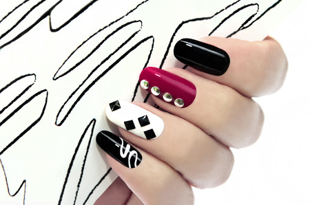Graphic manicure with black,Burgundy,white varnish and decorative ornaments on the nails  Stock Photo