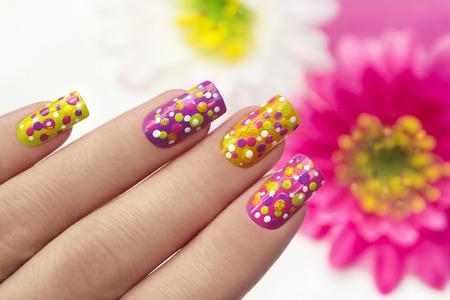 Maniküre mit mehrfarbigen Lack für die Nägel und das gleiche Design in Form von Punkten auf Frauen Hand