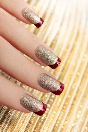Brilliant Golden manicure with red lacquer on the end of the nail  스톡 콘텐츠