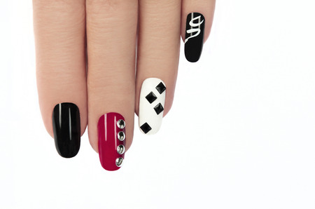 Glamorous manicure with different colors of paint and rhinestones square and round shapes on a white background  photo