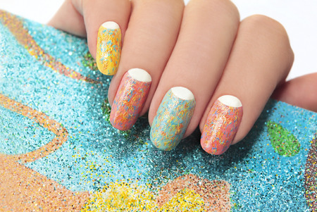 Pastel manicure with different colors of paint and coating in the form of colorful polosochku with stripes