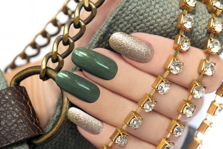 Green manicure with a brilliant gold lacquer on oval shaped nails with the accessory in hand  photo