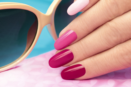 gel:     Pink manicure covered different in tone nail Polish on oval shaped nails