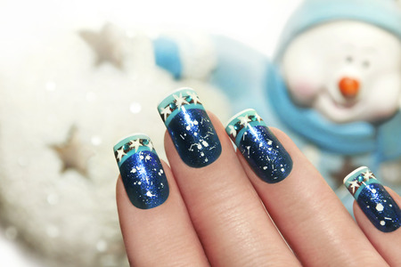Snow winter manicure with white sequins and rhinestones in blue, brilliant Polish on the background of the snowman.