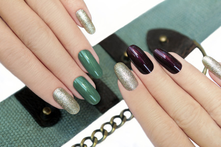 Green brown manicure with Golden shiny varnish on the background of the accessory. Standard-Bild