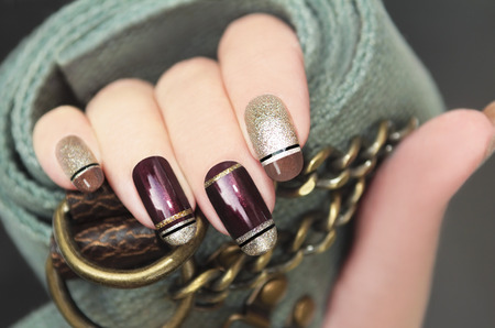 Golden brown French manicure with black stripes on the background of the accessory.