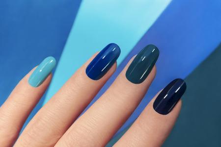 Blauwe manicure in lichte en donkere kleuren van de lak op een gestreepte achtergrond.