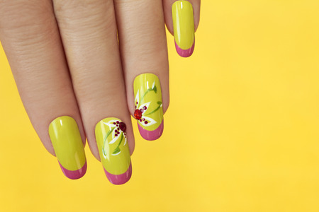 French green manicure with design of flowers with rhinestones on a yellow background.