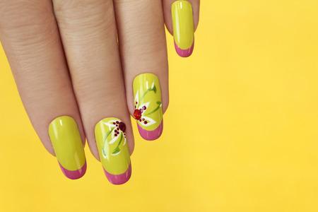 Franse groene manicure met ontwerp van bloemen met strass steentjes op een gele achtergrond.